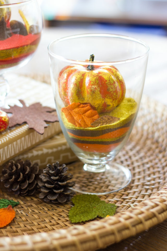den Tisch herbstlich arrangieren, Glasbecher mit kleinen Kürbissen und Dekoblättern füllen, Herbststimmung im Wohnzimmer