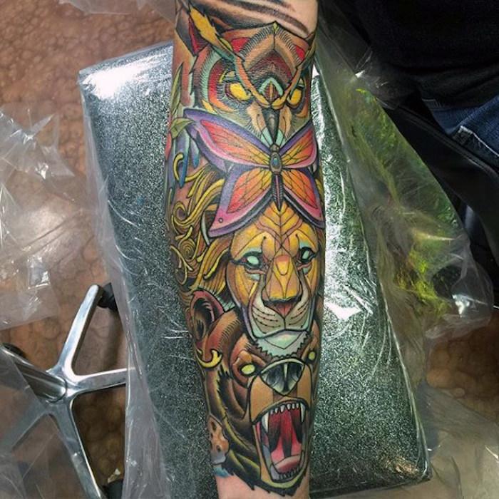 tattoo oberarm, farbige tätowierung mit löwe, bär und eule