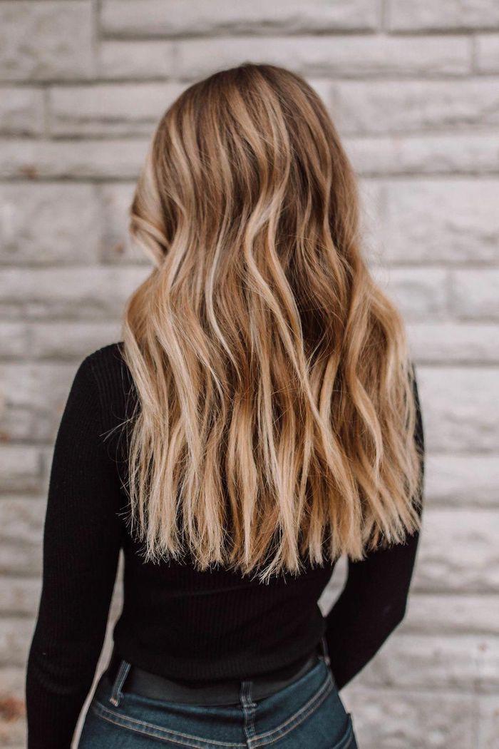 Gewellte blonde Haare mit helleren Strähnen, lange offene Haare, schwarze Bluse und Jeans