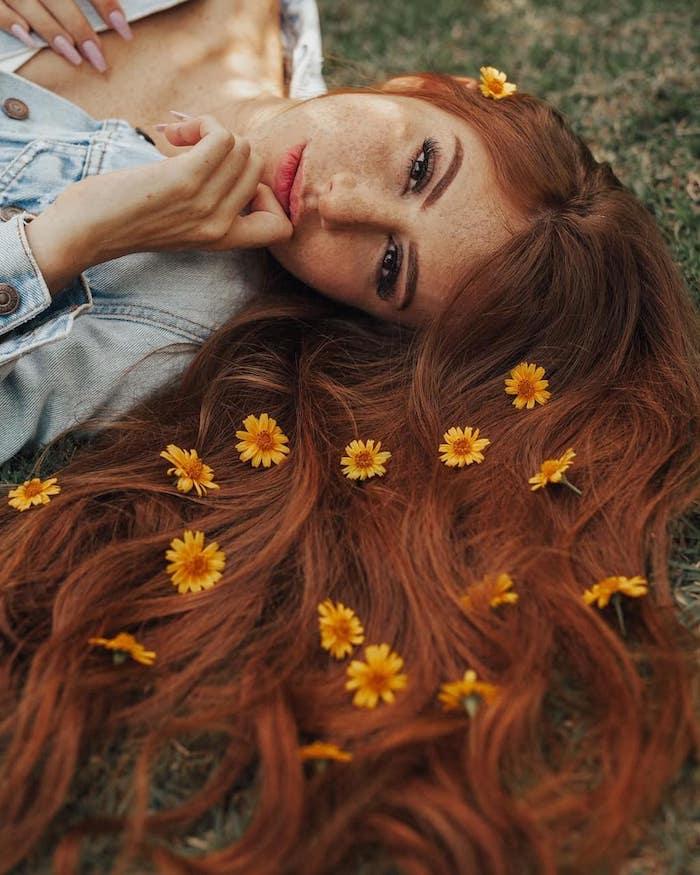 Haarfarbe Kupfer, lange gewellte Haare, gelbe Blüten darauf, Denim Jacke, leichtes Make up