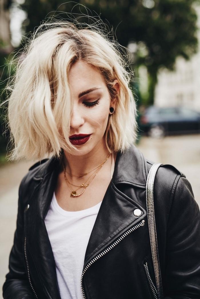 Platinblonde Haare, kinnlanger Bob Haarschnitt symmetrisch mit Seitenscheitel, weißes Shirt und schwarze Lederjacke, roter Lippenstift