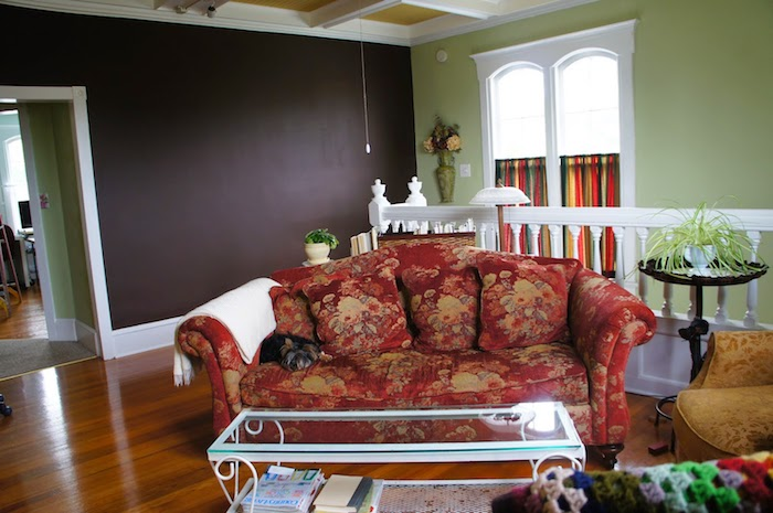 ein buntes Sofa mit Blumenmuster und eine Wand in Tafelfarbe im Wohnzimmer