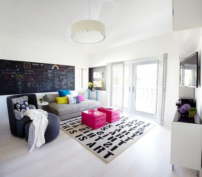 ein gemütliches Wohnzimmer mit eine Wand in Tafelfarbe, worauf viele Aufschriften stehen