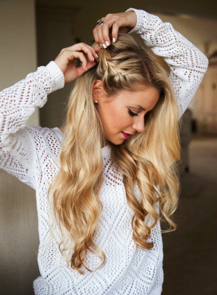 Lange gewellte Haare, halboffene Flechtfrisur, weißer Pullover und weißer Nagellack, roter Lippenstift