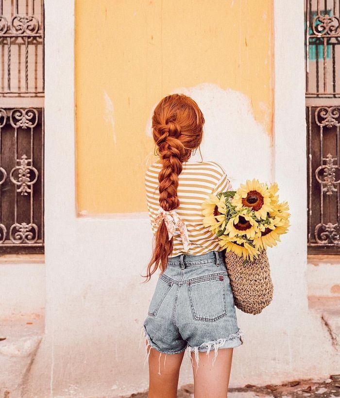 Lange geflochtene Haare, Haarfarbe Kupfer, Denim Shorts mit hoher Taille und gestreiftes T-Shirt, Sonnenblumen in Rattan Korb