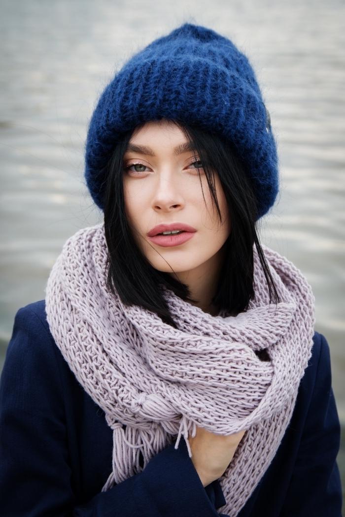 Schwarze Haare, lilafarbener Schal und dunkelblaue Mütze, leichtes Make-up, dunkelblauer Mantel