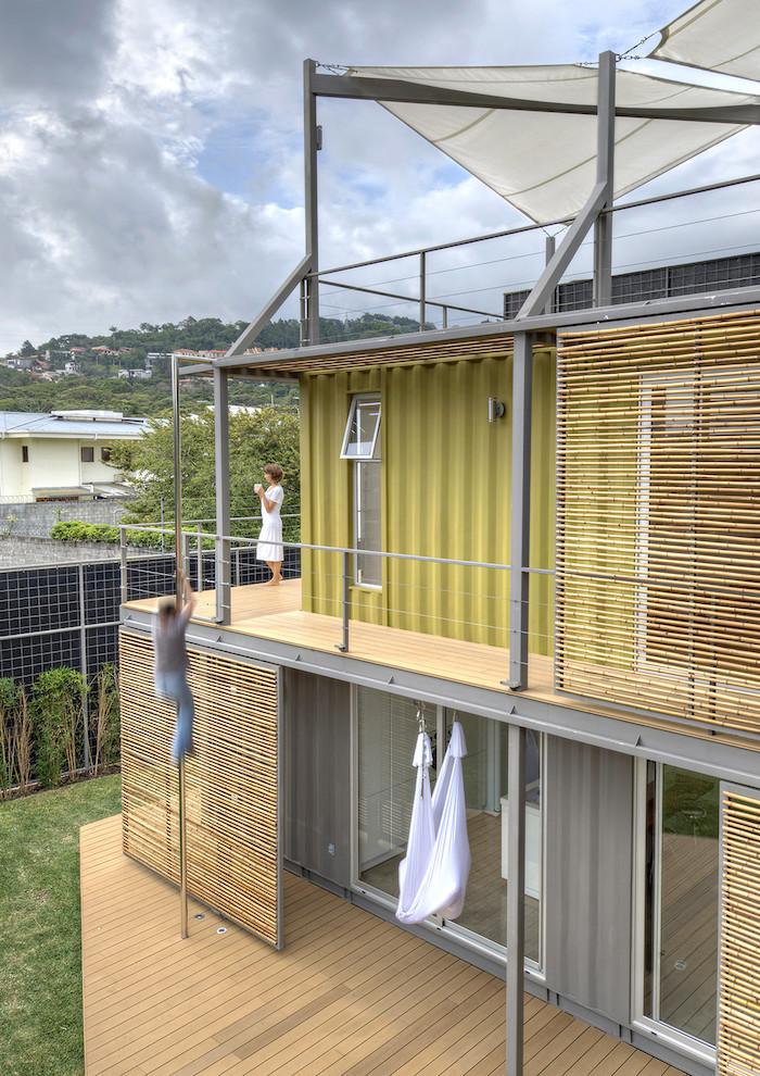 noch ein schönes zweistöckiges haus aus containern mit einer terrasse und zwei menschen