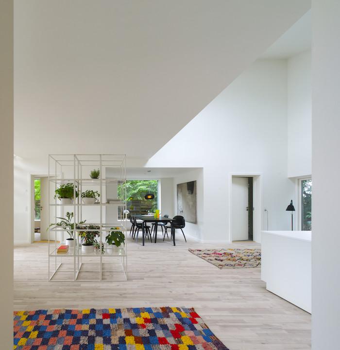 hier finden sie ein schönes zimmer eines container hauses mit weißen wänden, schwarzen stühlen, tisch und grünen pflanzen