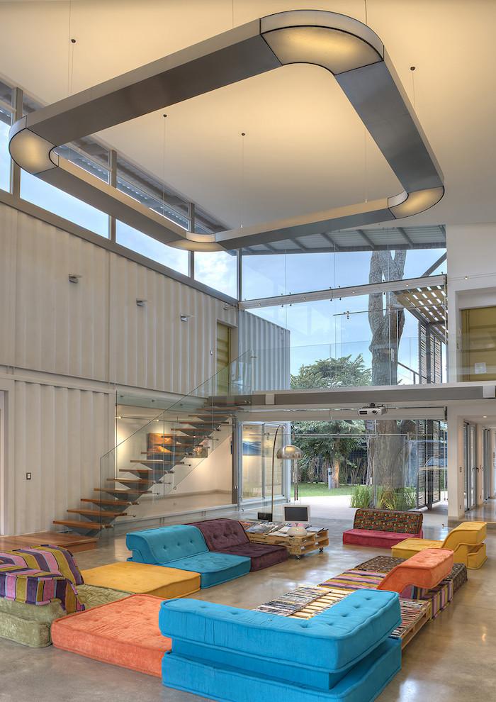 inspirierende ideen für ein schönes zweistöckiges haus- ein zimmer mit treppe und blauen, gelben und orangen sofas