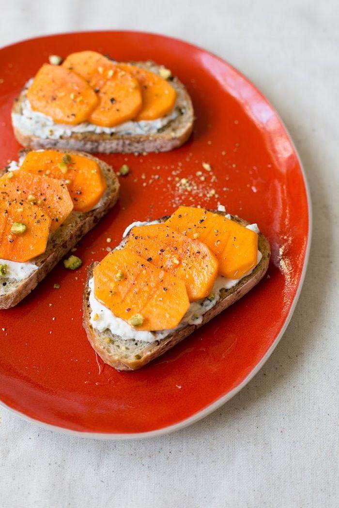 wie isst man kaki, scheiben brot mit persimonenscheiben und weißem käse