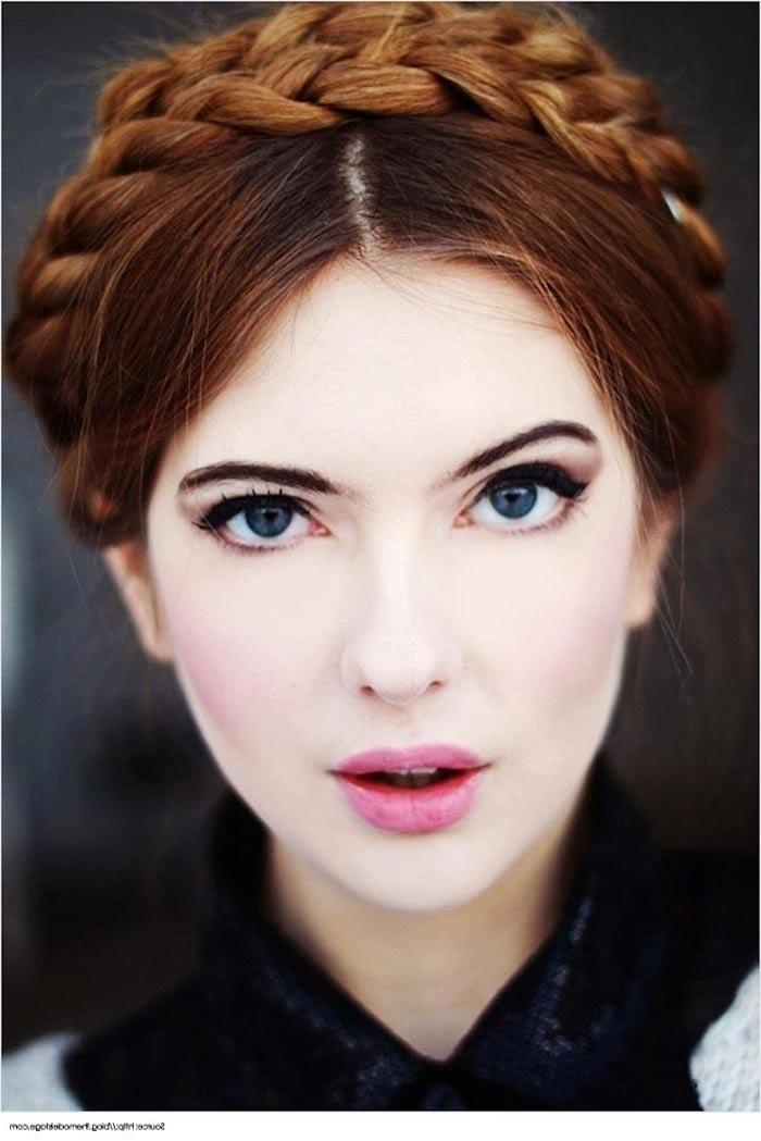 eine rothaarige Schönheit mit blauen Augen und rosa Lippenstift und Frisur mit Haarband