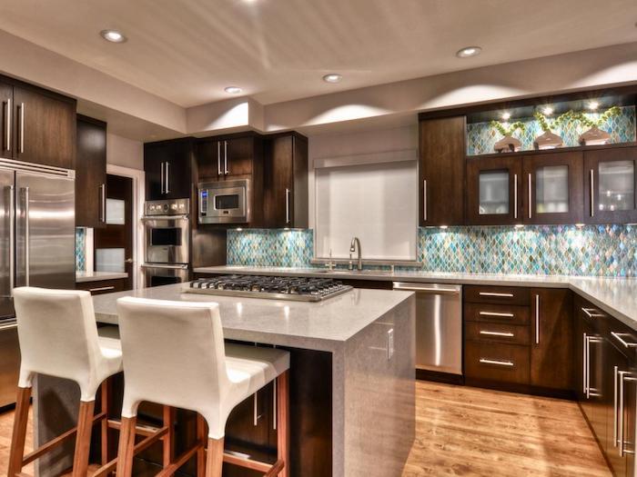 offene Küche mit geometrischen Mosaikfliesen in vielen Farben, eine Kochinsel und Tecke