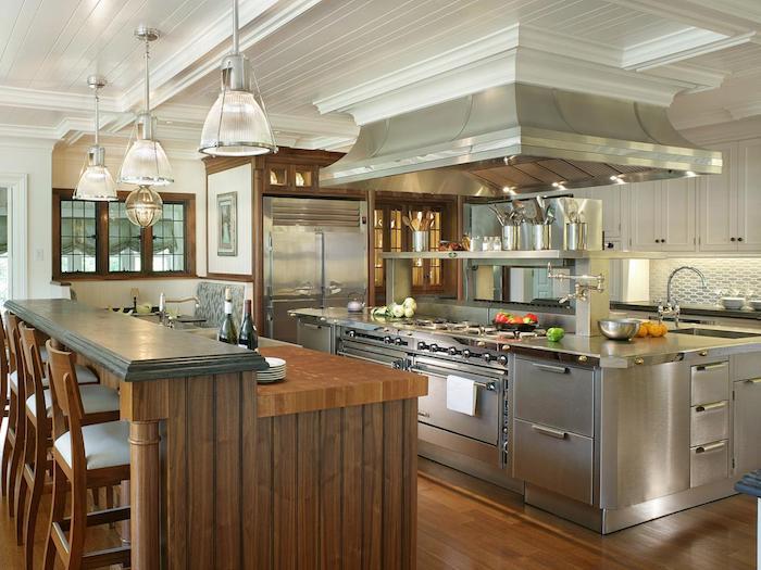 viele moderne Geräte in silberner Farbe in einer offenen Küche, Theke aus Holz
