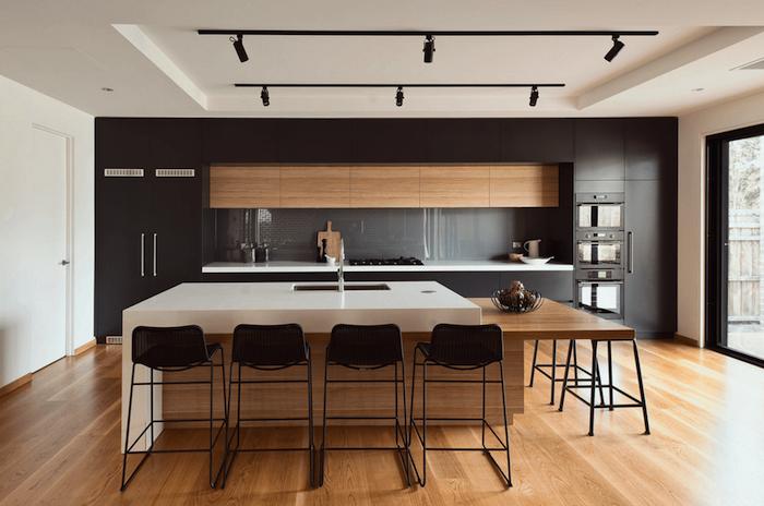 weiße Theke und Kochinsel in offenen Küche, schwarze Regale und Laminatboden