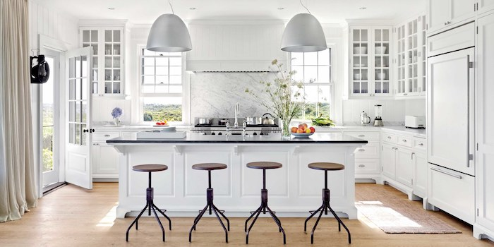 weiße Wohnküchen mit Arbeitsplatte aus Glas und zwei Lampen, Laminatboden