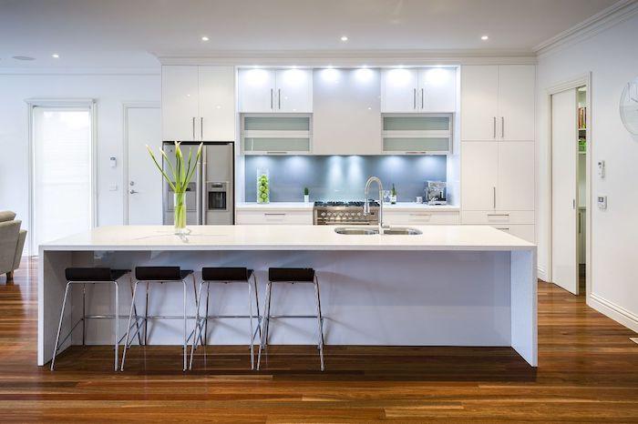 Wohnküchen in weißer Farbe mit schwarzem Hocker und mit indirektem Licht