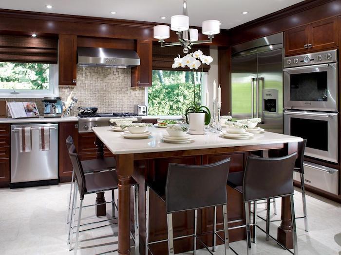 Wohnküchen, ein Tisch für den Frühstück gedeckt, drei eingebaute Herde, Mosaikfliesen an der Wand