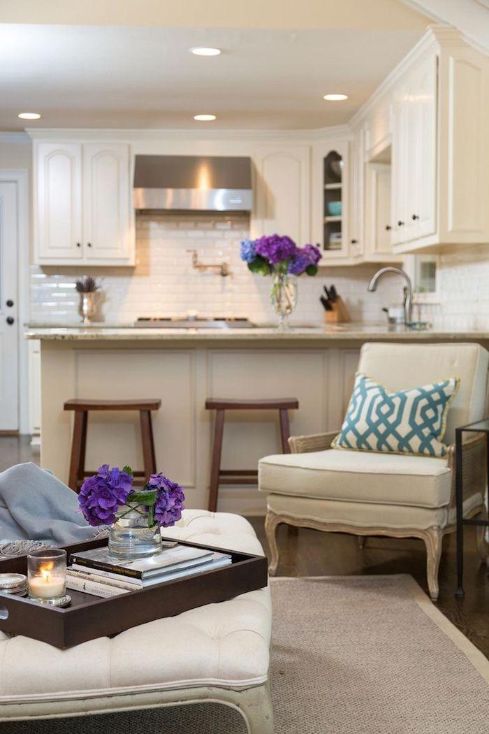 zwei Vasen mit lila Blumen Sofa und Hocker und eine Theke in der Wohnküchen