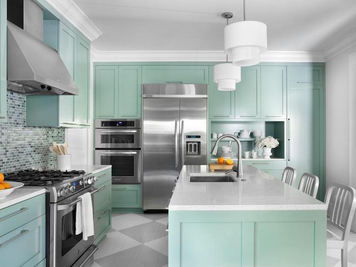 Wohnküchen in hellgrüner Farbe, Mosaikfliesen an der Wand, weiße Marmor Arbeitsplatte