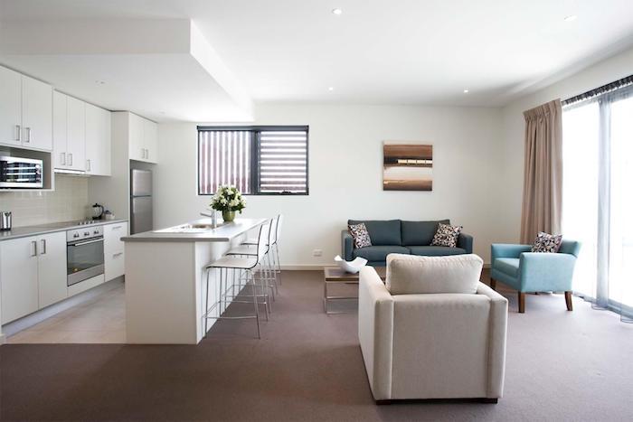 Offene Küche mit Wohnzimmer - weiße Küche und bunte Sessel, beige Vorhänge