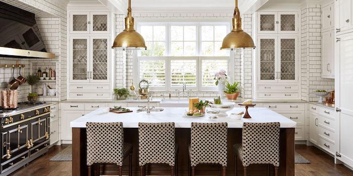 eine Luxus Wohnküche mit zwei Lampen in goldenen Farben, weiße Arbeitsplatte