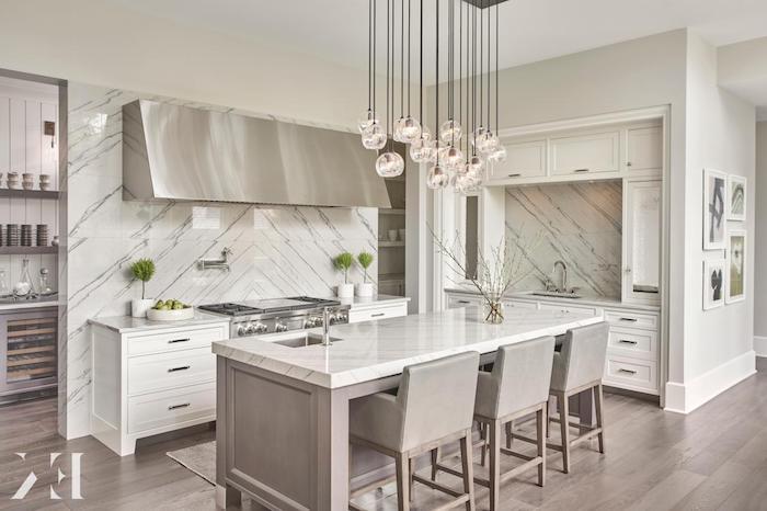 Wohnküche voller Marmor und graue Stühle, kleine Schubladen, moderner Herd