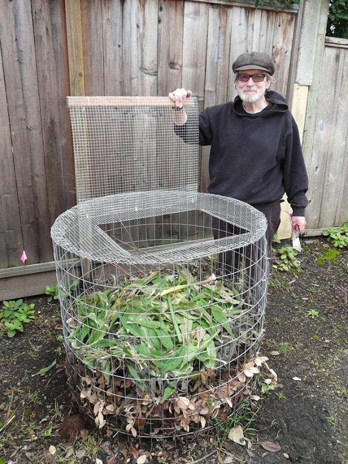 hier ist ein bild mit einem alten mann mit brillen und seinem großen selbstgebauten komposter aus metall