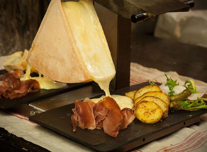 raclette zutaten raclette käse schmelzt in die teller kartoffeln fleisch speck kräuter