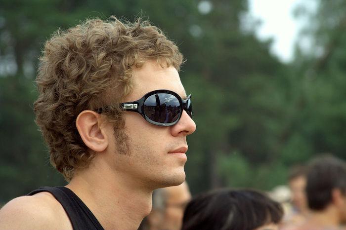 blonder Jugendlicher mit lockigen Haaren und Koteletten, Open Air Event im Park