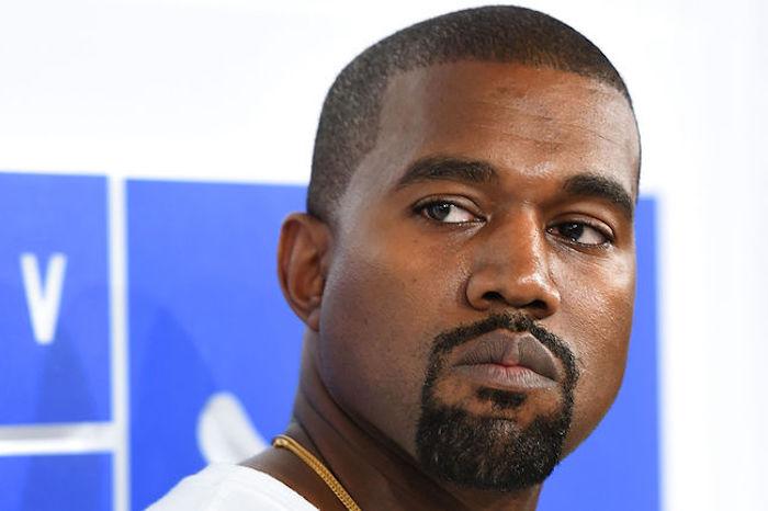 Kanye West mit Henriquatre auf einem offiziellen Anlass, blaue Poster, weiße Wand