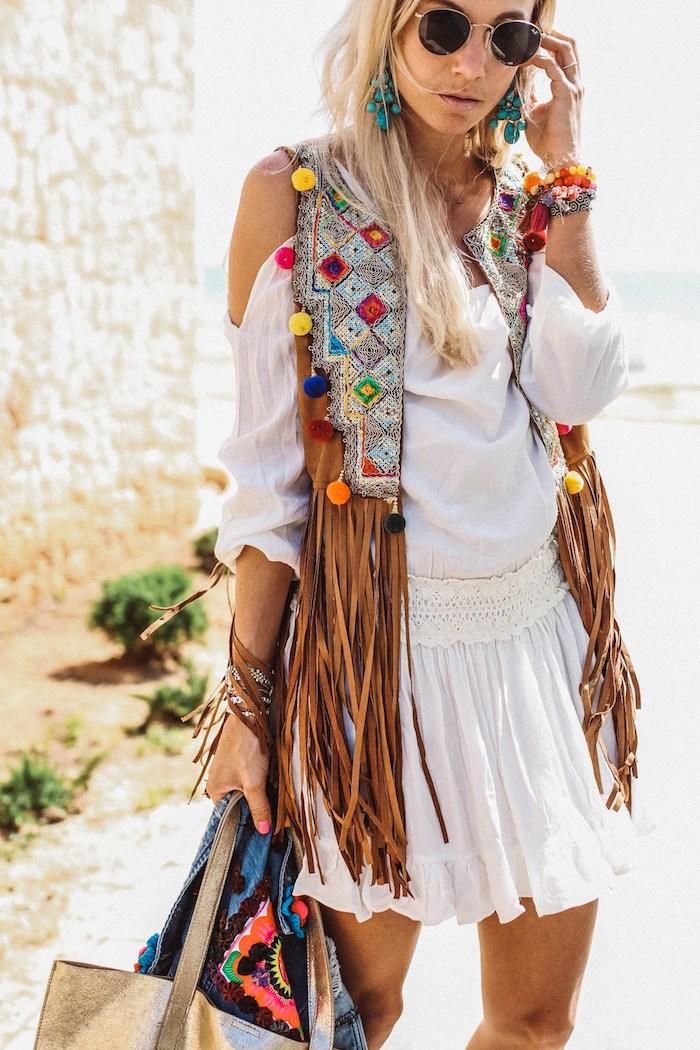 hippie kleider, dame mit weißer bluse, weißem rock und hellbrauner weste mit fransen und bummeln