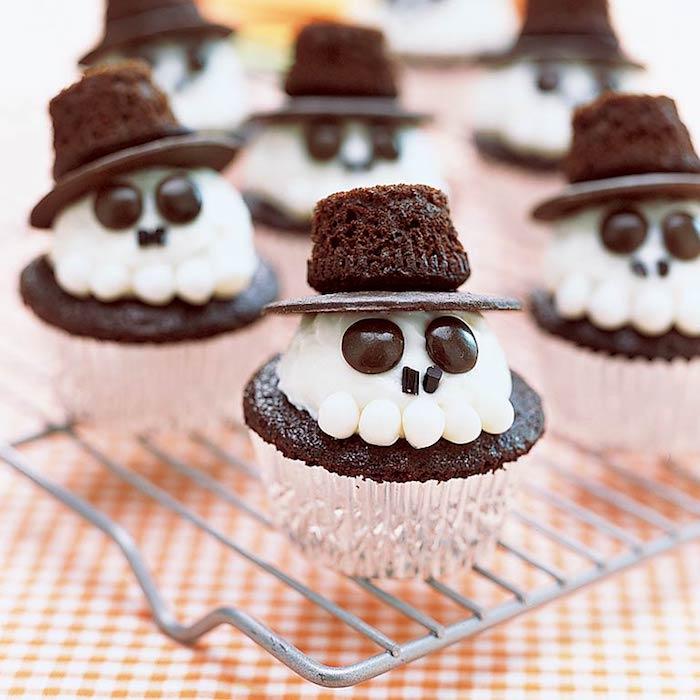muffins dekorieren, schädel aus buttercreme mit augen und hüten aus schokolade
