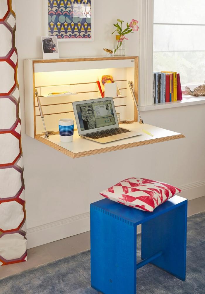 Schreibtisch für kleine Räume, funktionelle und praktische Ideen, blauer Holzhocker, weiß-rotes Kissen, Bücher am Fenster, Laptop und Porzellantasse auf dem Tisch