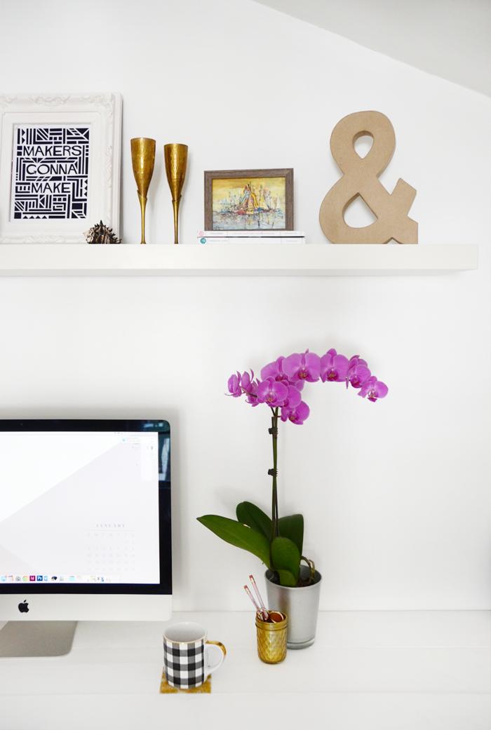 Weißer Schreibtisch, lila Orchidee, schwarzweiße Porzellantasse, Holzregal, kleine Gegenstände darauf