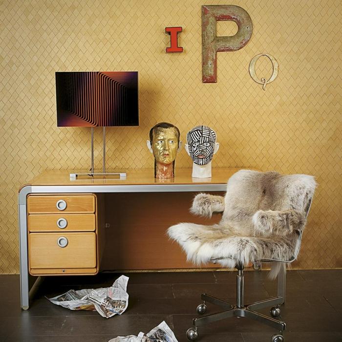 Arbeitszimmer mit Vintage Einrichtung, Schreibtisch aus Holz, Stuhl, bedeckt mit Pelz, Zeitungsblätter am Boden, zwei Skulpturen auf dem Tisch