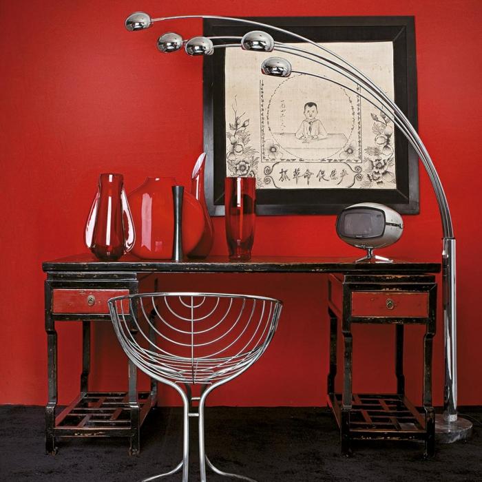 Arbeitszimmer mit Vintage Einrichtung, knallrote Wände, Holzisch mit Altersspuren, silberne Stehlampe und Stuhl, rotes Porzellan