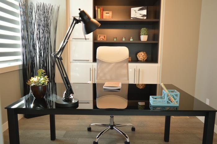 Arbeitszimmer in Creme, schwarzer Schreibtisch, blauer Stifthalter, kleine Grünpflanze, weißer Schrank mit schwarzen Regalen