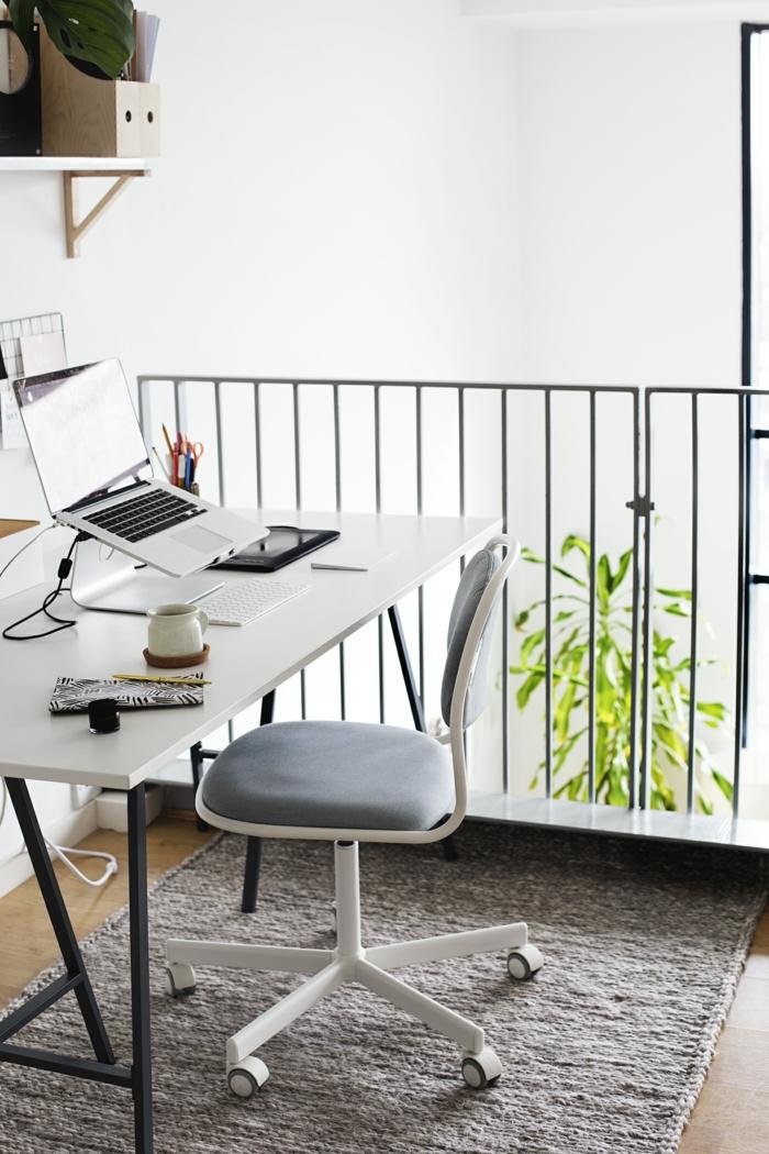 weißer Schreibtisch mit schwarzen Beinen, Laptop, Stifhalter und Teetasse darauf, grauer Teppich