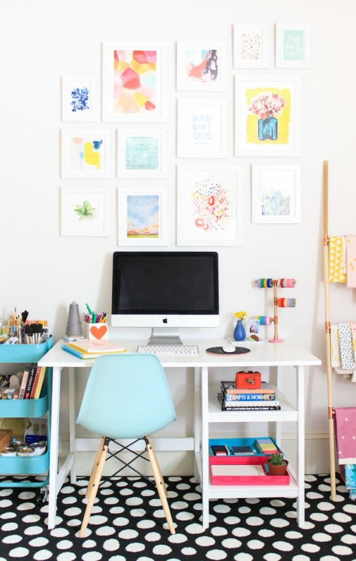 Arbeitszimmer Einrichtung, viele Gemälden an der Wand, schwarzer Teppich mit weißen Punkten, weißer Schreibtisch und blauer Stuhl