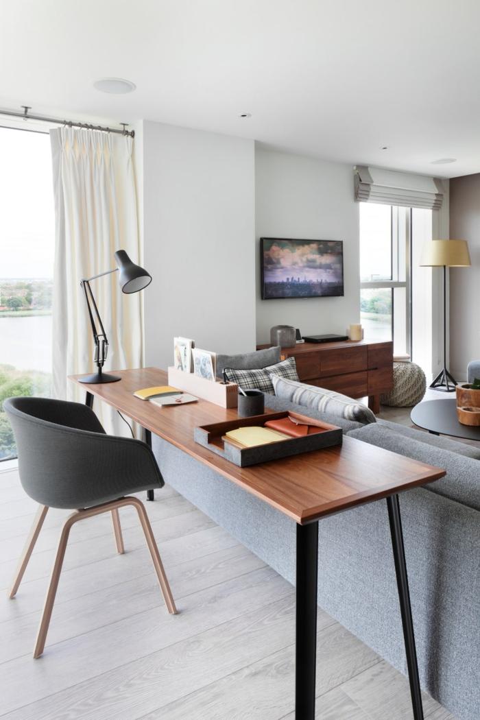 Wohnzimmer dient als Arbeitszimmer auch, Holztisch, schwarzer Stuhl aus Kunststoff, graues Sofa mit Dekokissen