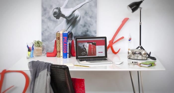 weißer Schreibtisch, Ballerina-Bild an der Wand, dicke Bücher, Vintage Nachttischlampe und Telefon, Laptop
