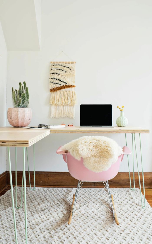 Arbeitszimmer Einrichtungsideen, rosa Kunststoffstuhl, bedeck mit Pelz, zwei kleine Schreibtische aus Holz, großer Kaktus im Blumentopf, kleiner Blumenstrauss, Laptop und Heft