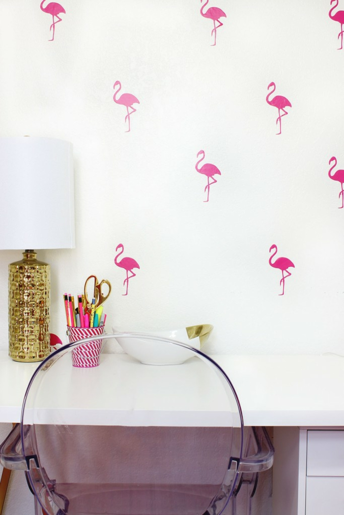 Arbeitszimmer einrichten, weiße Wand mit kleinen Flamingos, Holz-Schreibtisch, durchsichtiger Kunststoffstuhl, Vintage Nachttischlampe, Stifthalter