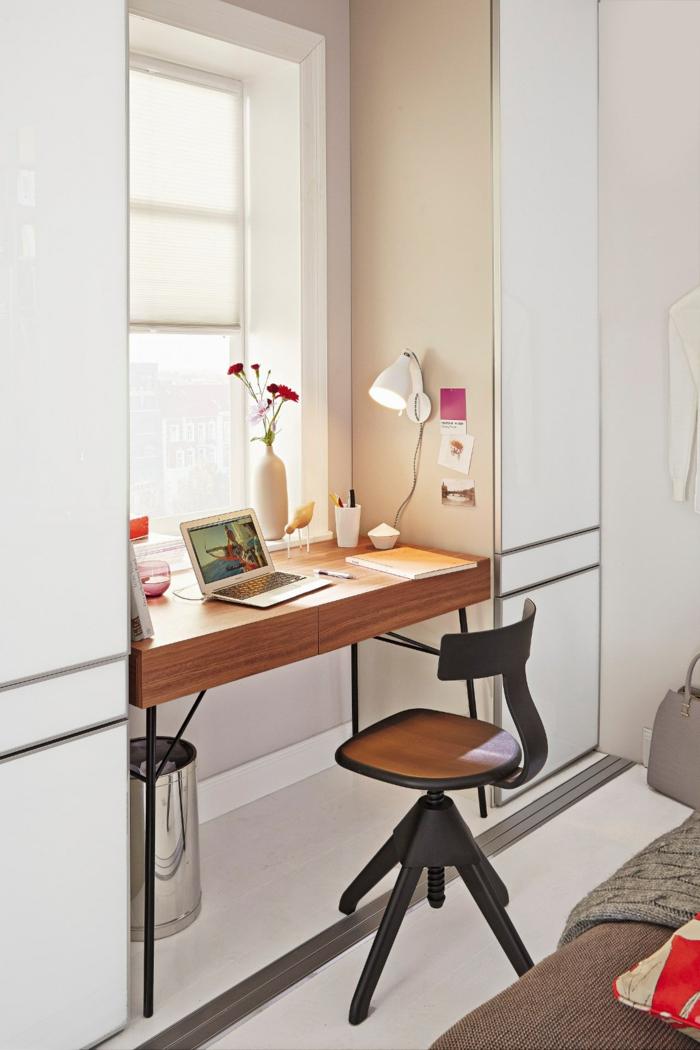 praktische Idee für kleine Räume, Schreibtisch am Fenster, weiße Vase mit Nelken, weiße Nachttischlampe an der Wand, gelbes Heft und Kugelschreiber