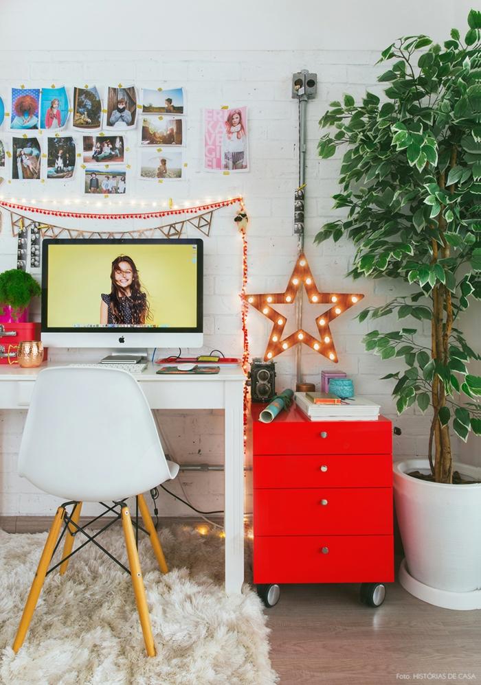 buntes Arbeitszimmer, weißer Schreibtisch und grellrote Schublade, große Grünpflanze, Fotos an der Wand, leuchtender Stern