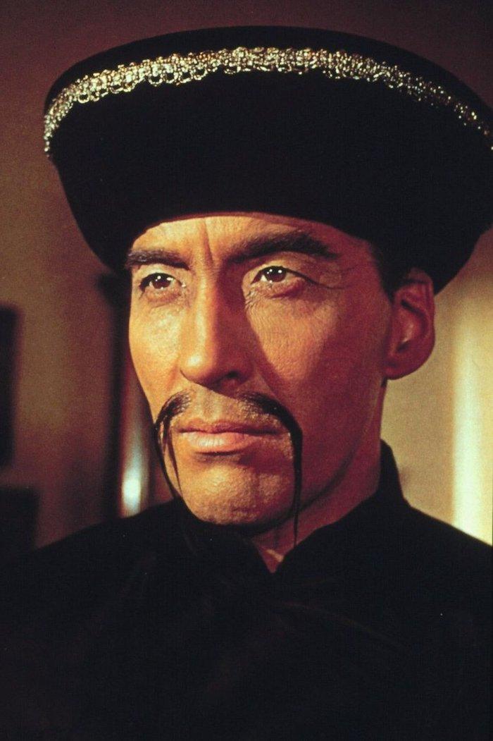 Dr. Fu Manchu mit langem Schnurrbart in einem Zimmer mit gelbem Licht
