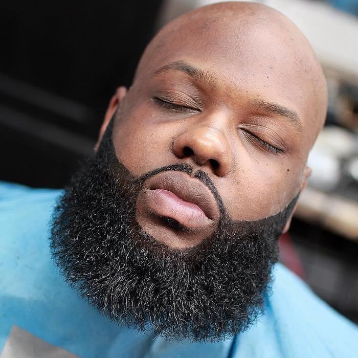 Afroamerikaner mit kahl rasiertem Kopf, Bartfrisur mit strikten Konturen, blauer Friseurumhang