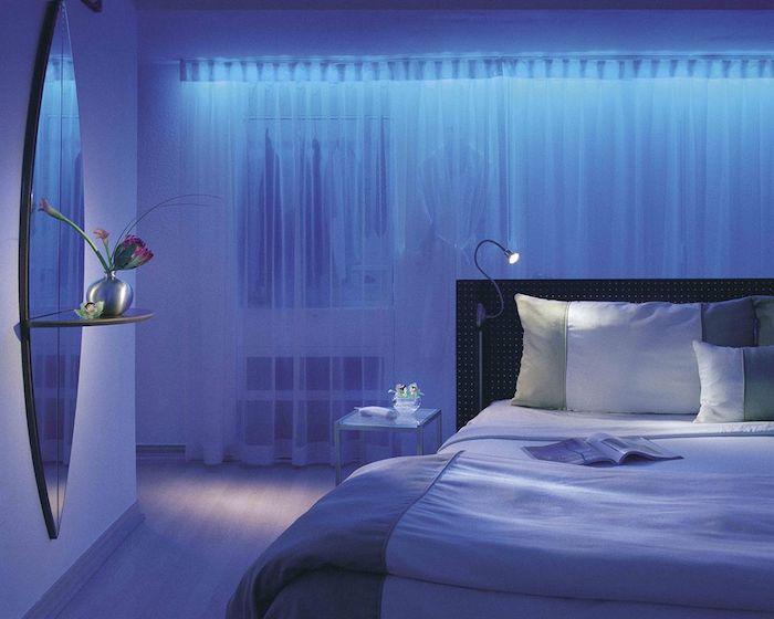 blaues Schlafzimmer mit indirekter Beleuchtung, weiße halbdurchsichtige Vorhänge