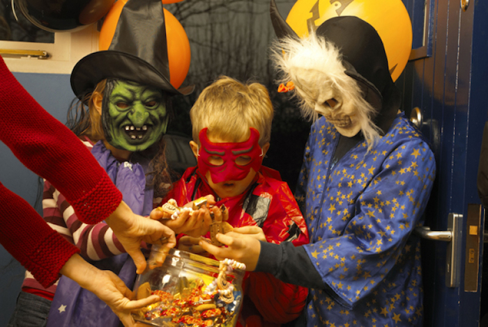 Halloween Bilder - ein paar Kinder mit gruseligen Masken die Süßigkeiten sammeln