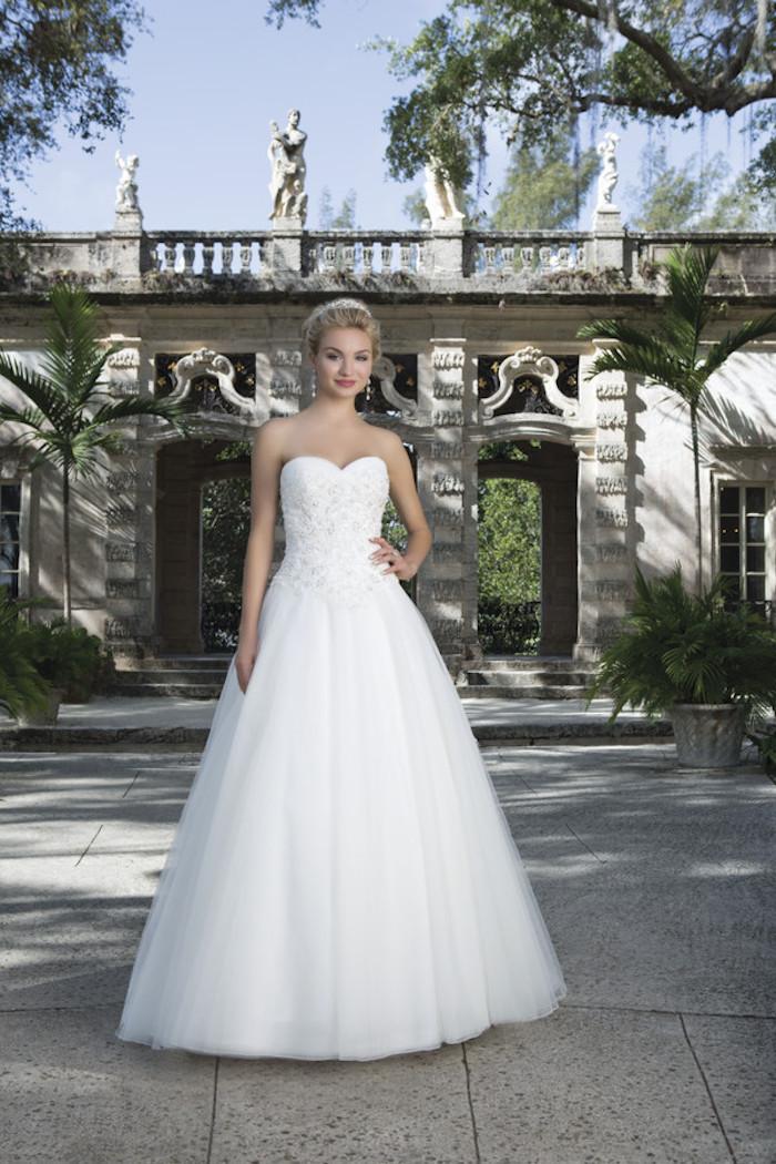 eine Braut mit einem schönen Hochzeitskleid vor einem Bogen - Brautmode